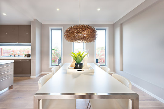 Interior of a modern dinning room with a long white table and ba