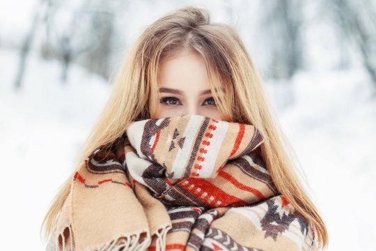 Young happy woman wearing winter cloth. Scarf on the face