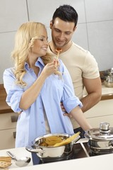 Loving couple tasting sauce in kitchen