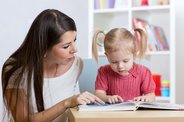 kid girl and mother read a book indoors