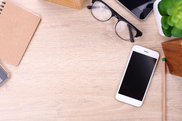 smartphone, tablet and office supplies on wooden background