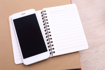 Blank screen smartphone and note book on wooden background