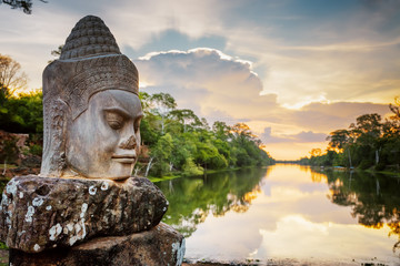 Wall Mural - Stone face Asura and sunset over moat. Angkor Thom, Cambodia