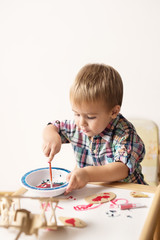 Adorable kid playing on his table with watercolors, painting a wooden parts of his airplane wooden toy. He is young designer with many ideas waiting to be found. Shallow depth of field.