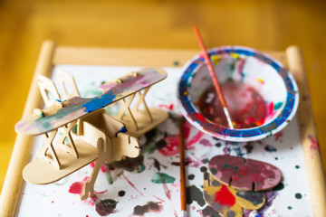 Table with watercolors, brushes,and wooden parts of airplane toy. Young designer with many ideas waiting to be found. Shallow depth of field.