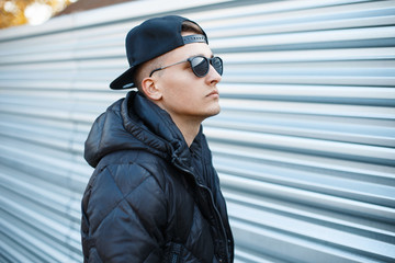 Young handsome man in a black cap and sunglasses in a warm jacket on a background of metal wall