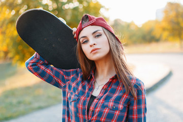 Closeup portrait of a young girl in a cap holding a skateboard in the park at sunset.