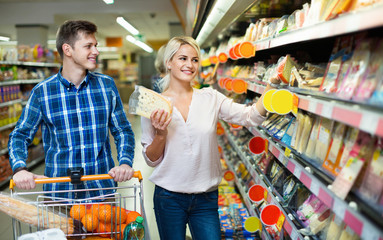Young spouses buying cheddar in cheese section