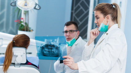 Consultation at dentist office. Female doctor consults handsome doctor in background. Shallow depth of field.