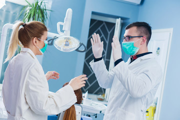 Two doctors consults before surgery at dentist office.