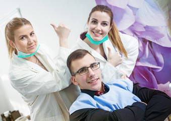 Patient enjoying at dentist chair in dentist office. Two attractive female doctors showing thumbs up in background.