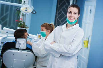 Portrait of beautiful dentist at office. Doctor and patient in background. Empty space for text.