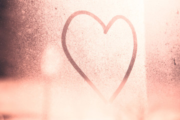 Red color shine abstract blurred love heart symbol drawn by hand on the frozen glass window with soft bright red color background. Selective focus and rose quartz pastel pantone color used.