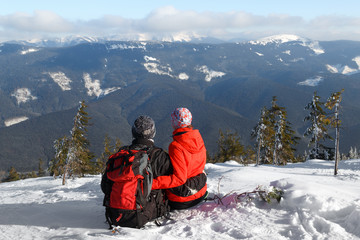 Romantic scene of happy young romantic couple sitting with natural mountain background. Love concept.