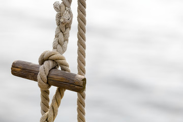 Nautical rope, knot and wooden peg for a maritime background with copy space