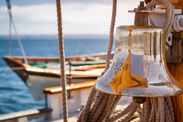 Brass ship bell on a classic big wooden sailboat at sea. Close up