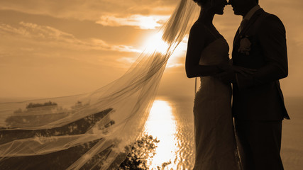 Silhouette couple kissing over sunset background.