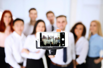 Young people making group photo with smart phone in office