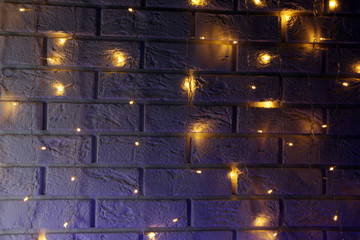 Electric garland on white brick wall background