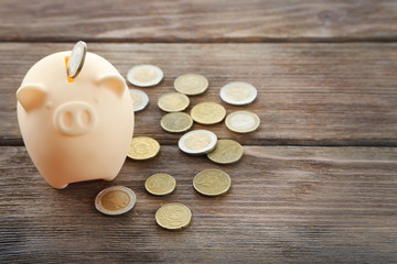 Piggy bank with coins on wooden background