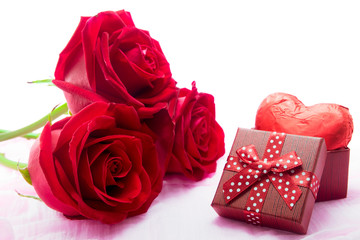 Red roses and chocolate heart shape presents on fabric