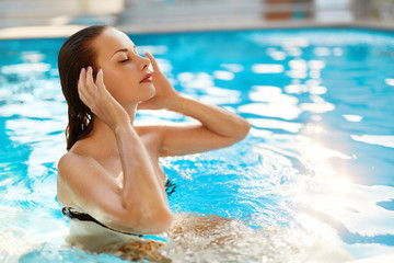 Body Care. Freshness Concept. Beautiful Sexy Young Woman Relaxing In Swimming Pool ( Water ) At Resort Spa Hotel. Health Care, Beauty Concept. Healthy Lifestyle, Wellness. Summer Travel Vacation.