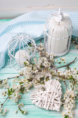 Background with white spring blossom  of trees, decorative heart  and candles in  bird cages on turquoise painted wooden planks.  Selective focus is on heart.