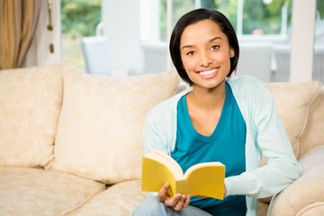 Smiling brunette reading a book on the sofa