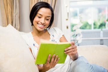 Smiling brunette reading a book