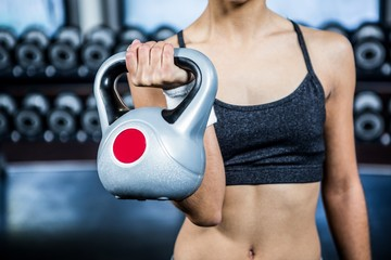 Cropped image of fit woman lifting kettlebell