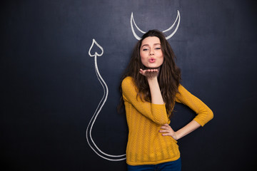 Cute woman with devils horns and tail drawn on blackboard