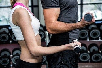 Cropped image of fit couple lifting dumbbells