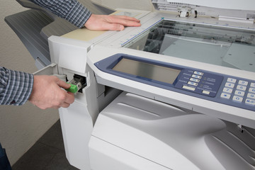 Midsection of businessman fixing cartridge in photocopy machine