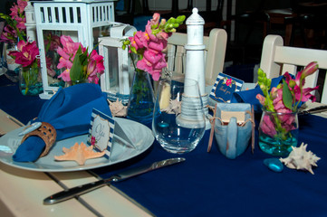 Festive table setting with starfishes, napkins, glasses and candles, bright summer table decor