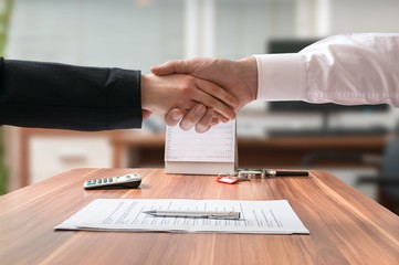 Shakehand of lawyer and business woman sitting behind desk with agreement on blurred background.