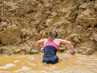 Back view of woman climbing up dirty wall from puddle