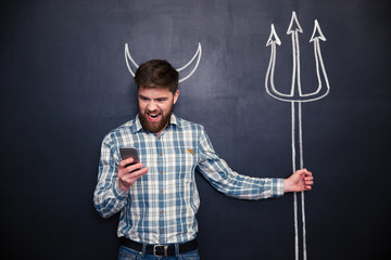 Handsome man playing role of devil standing over blackboard background