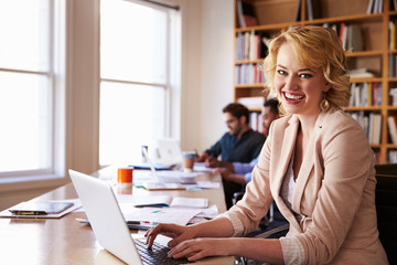 Businesswoman Using Laptop At Desk In Busy Office
