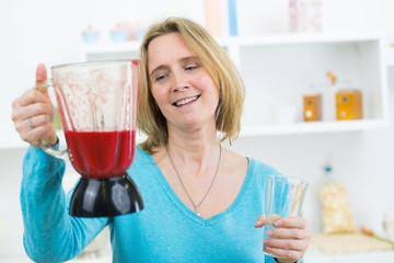 frau macht smoothies selbst