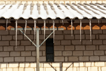 Icicles on the roof of brick house.