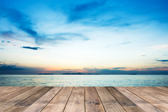 Perspective of wood terrace against beautiful seascape at sunset