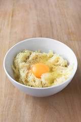 Raw grated potatoes and egg in white bowl