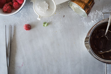 Metal countertop surface with different staff for dessert plating: fresh raspberries, chocolate sauce, sugar powder, lemon balm
