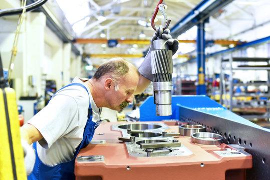 älterer Arbeiter bei der Montage von einem Getriebe in einer Fabrik // Workers in mechanical engineering in a factory mounted a gear