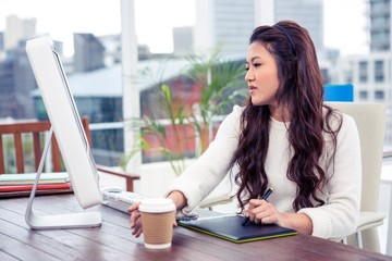 Focused Asian woman using digital board and computer