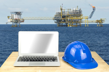 laptop and blue safety helmet on wood table with rig background