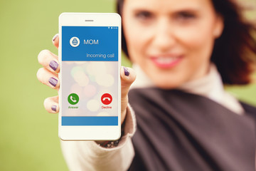 Incoming call from mom in a mobile phone. Woman holding a mobile and showing the screen to the camera.