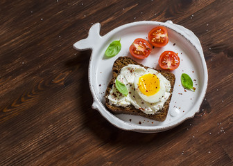 Open sandwich with feta cheese and boiled egg, tomatoes, and basil on a white plate on a wooden surface. Healthy breakfast or snack