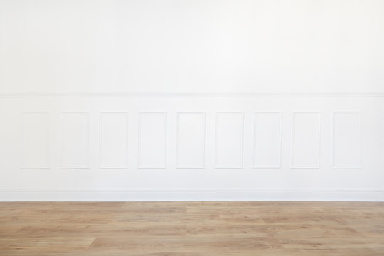 Empty white room with wooden floor and wood trimmed wall