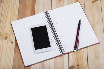 White Smart Phone With Blank Black Screen, Notepad And Pencil On Wooden Desk.